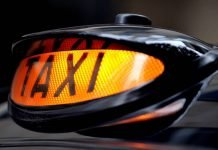 Illuminated taxi sign on a black cab